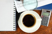 Cup of coffee on worktable covered with documents close up — Stock Photo
