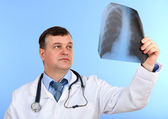 Medical doctor analysing x-ray image on blue background — Stock Photo