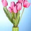 Beautiful bouquet of pink tulips in vase, on blue background — Stock Photo