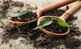 Secco tè con foglie verdi in cucchiai di legno, sullo sfondo della tela da imballaggio — Foto Stock
