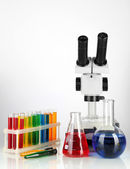 Test tubes with colorful liquids and microscope isolated on white — Stock Photo