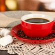 Stock Photo: Cup of coffee with scarf on table in room