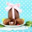 Composition of Easter and chocolate eggs on blue fabric background - Foto Stock