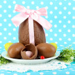 Composition of Easter and chocolate eggs on blue fabric background - Stockfoto