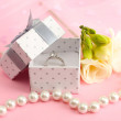 Beautiful box with wedding ring and flower on pink background — Stock Photo