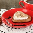 Chocolate cookie in form of heart with cup of coffee on wooden table close-up - Stockfoto