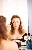 Jonge mooie vrouw maken make-up in de buurt van spiegel — Stockfoto