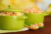 Rice porridge with pumpkin in saucepans on wooden table, on green background — Foto Stock