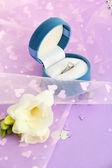 Alyans ve mor zemin üzerine çiçek güzel kutusu — Stok fotoğraf