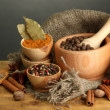 Mortar, bowls and spoons with spices, on table on grey background — Stock Photo