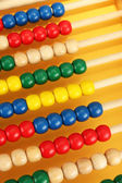Bright wooden toy abacus, on yellow background — Stock Photo