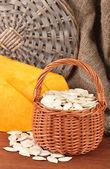 Pumpkin seeds in wicker basket, on wooden background — Stock Photo