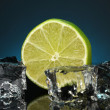 Stock Photo: Ice cubes with lime on darck blue background