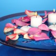 Rose petals and candles in water in vase on blue background close-up — Stock Photo #21019527