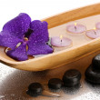Spa stones and wooden bowl with candles and purple flower, on wet background — Foto de Stock