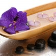Stock Photo: Spstones and wooden bowl with candles and purple flower, on wet background