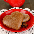 Chocolate cookies in form of heart with cup of coffee on wooden table close-up — Stock Photo