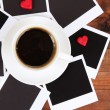 Cup of coffee on worktable covered with photo frames close up — Stock Photo #21020625