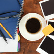 Stock Photo: Cup of coffee on worktable covered with photo frames close up