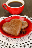 Chocolate cookies in form of heart with cup of coffee on wooden table close-up — Photo