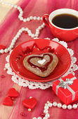 Chocolate cookie in form of heart with cup of coffee on pink tablecloth close-up — Photo
