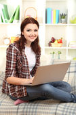 Beautiful young woman working on laptop on sofa in room — Stock Photo