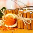 Decorative rose from dry orange peel and burning candles on wooden table — Stock Photo #21044057