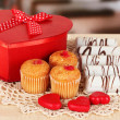 Sweet cookies with gift on table in cafe — Stock Photo