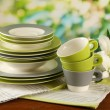 Stock Photo: Empty plates and cups on wooden table on green background