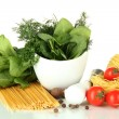 Composition of mortar, pasta and green herbals, isolated on white - Stock Photo