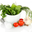 Composition of mortar, tomatoes and green herbals, isolated on white - Stock Photo