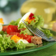 Fresh mixed salad with eggs, tomato, salad leaves and other vegetables on color plate, on bright background — Stock Photo