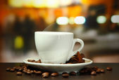 Cup of coffee with beans on table in cafe — Foto Stock