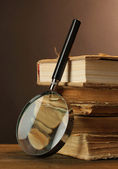 Magnifying glass and books on table — Stock fotografie