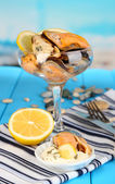 Cocktail of mussels in vase on wooden table on blue natural background — Stock Photo