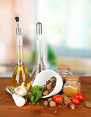 Composition of mortar, bottles with olive oil and vinegar, and green herbals, on bright background — Stock Photo