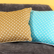 Colorful pillows on couch on yellow background — Stock Photo #21180313