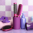 Hair brushes, hairdryer and cosmetic bottles in bathroom - Stock Photo
