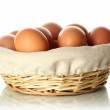 Stock Photo: Many eggs in basket isolated on white