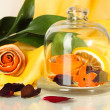 Decorative rose from dry orange peel in glass vase on yellow fabric background — Stock Photo