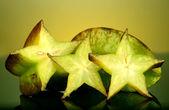 Two ripe carambolas on yellow background — Stock Photo