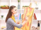 Beautiful young woman painter at work, on room interior background — Stock Photo