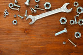 Bolts, screws, nuts and wrench on wooden table — Stock Photo