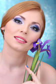 Beautiful young woman with glamour make up and flower on blue background — Stok fotoğraf