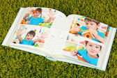 Open photo album with pictures on green carpet — Stock Photo