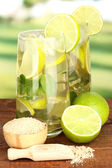 Glasses of cocktail with lime and mint on wooden table on bright background — Photo