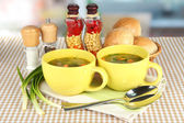 Fragrant soup in cups on table in kitchen — Stock Photo