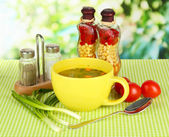 Fragrant soup in cup on table in garden — Stock Photo