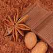 Chopped chocolate with cocoa, on brown background - Stock Photo
