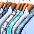 Shirts with ties on wooden hangers close-up — Stock Photo